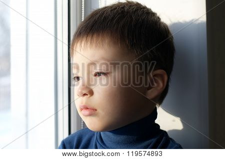 Boy Sitting On The Window With Sadness