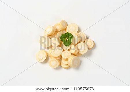 heap of sliced root parsley with leaves on white background