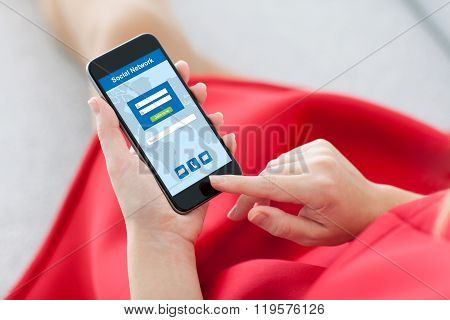 Woman In Red Holding Phone With Social Network On Screen