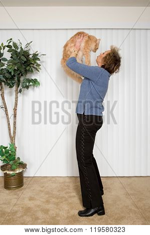 Senior woman holding pet cat