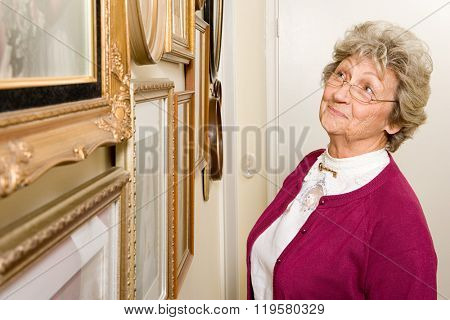 Woman looking at wall of photographs