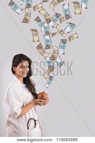 indian female doctor holding piggy bank or money box made up of clay and indian currency falling fro