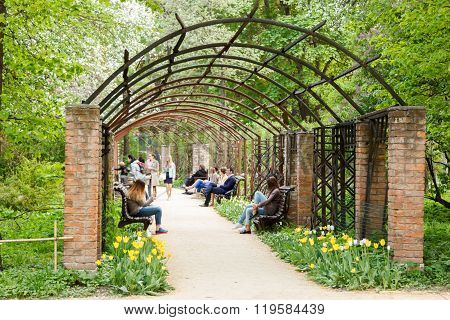People Walk Under Pergola In Moscow University Botanical Garden