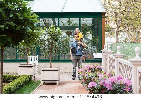 Girl Sitting On Daddy Shoulders In Garden