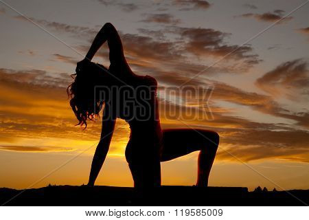 A silhouette of a woman on her knee bending back.