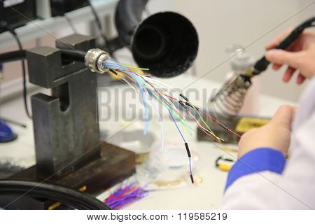 Factory Worker Assembles The Cable Connections