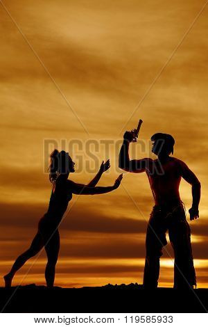 a silhouette of a woman reaching out to her cowboy that is holding his pistol.