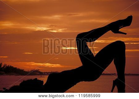 A silhouette of a woman relaxing on the beach.
