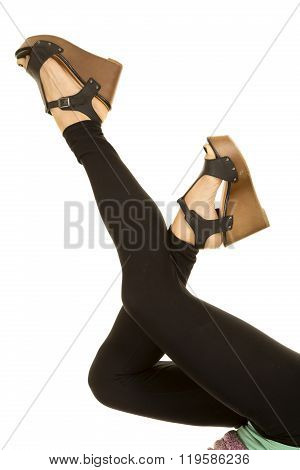 a woman with her legs up in her black leggins with shoes.