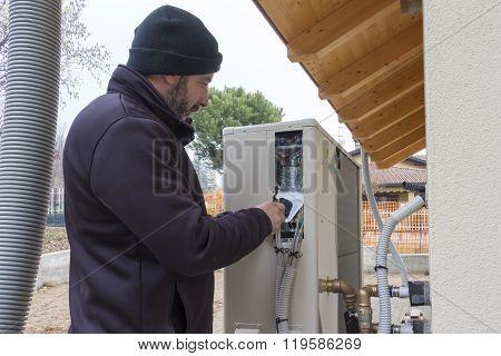 Plumber At Work Installing A Heat Pump