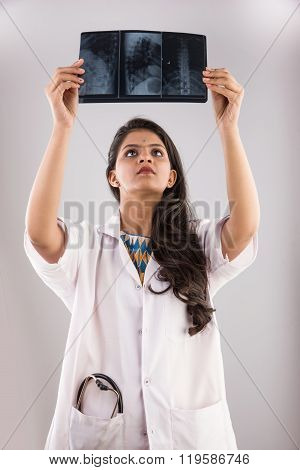 indian young medical practitioner examining xray or MRI scan, indian female doctor and x ray or MRI,