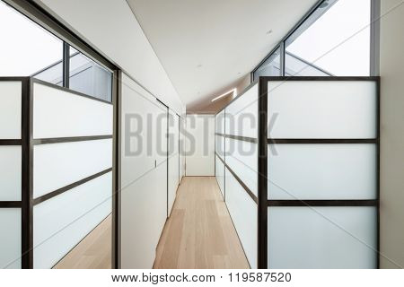 Interior of a modern house, long corridor with wall closets
