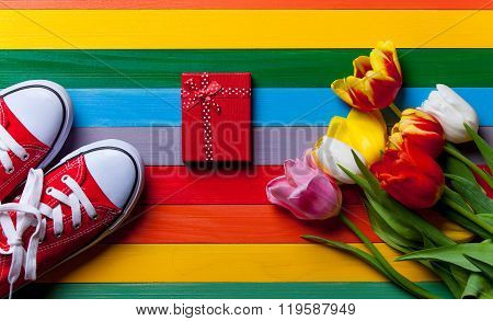 Bunch Of Tulips, Red Gumshoes And Gift Lying On The Table