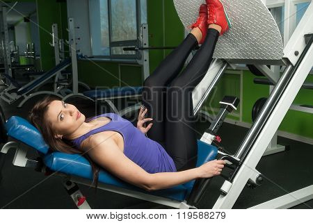 Fit woman training legs on leg simulator at gym
