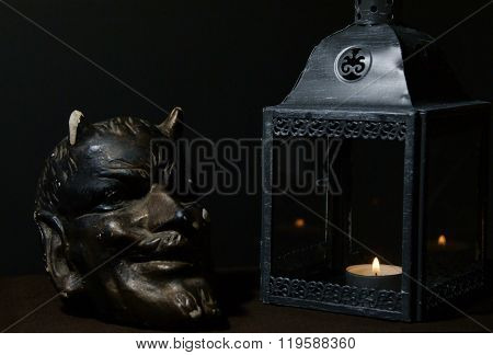 devilshead next to a gray lantern with a tealight.