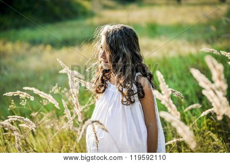 Beautiful Toddler Girl With Long Blond Hair Travels In Colorful Yellow Field