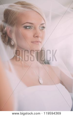 Portrait Of Beautiful Bride With Fashion Veil Posing At Home At Wedding Morning. Makeup. Blondegirl
