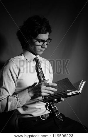 Young man reading a book with glasses.