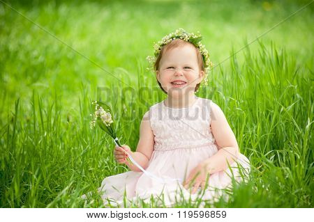 funny baby girl in wreath of flowers smiling outdoors