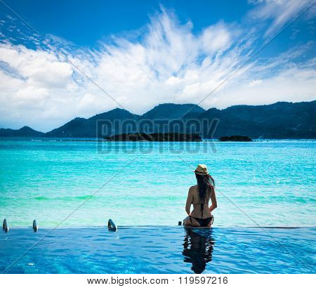 KO SAMUI, TAILAND-FEB 2, 2016: Young woman sitting at the edge of the swimming pool and watching at the sea on Feb 2. 2016 in Taianad.