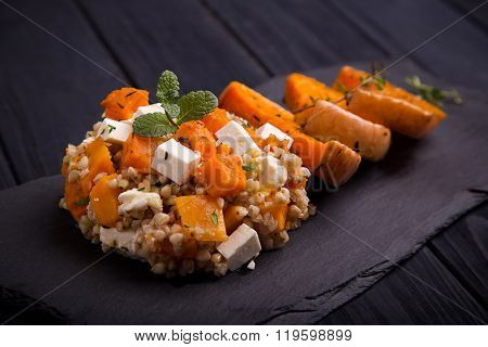 Baked pumpkin salad with feta cheese on black slate dish
