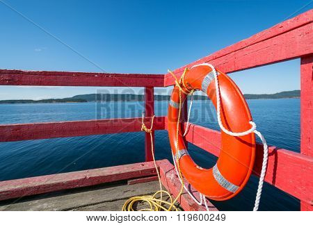 Red lifebuoy on a red ocean pier.