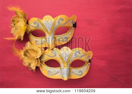 Colorful carnival mask on a red textured background. Masks with theater concept. Top view with copy space