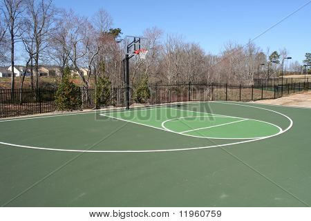 A green basketball court in a park