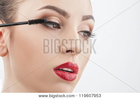 Cheerful young woman is applying cosmetic