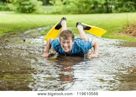 Happy Teen Trying To Swim In Muddy Puddle