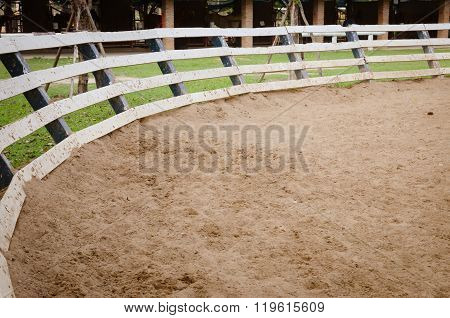 A horse training circle corral outdoors on the grass at an equestrian center.