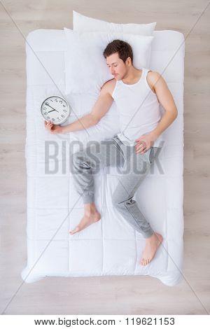 Pleasant man sleeping with clock