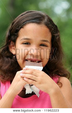 Young girl outside eating a candybar
