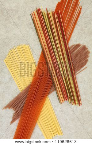 Dried spaghetti pasta food abstract background over natural hemp paper. Coloured varieties dyed with beetroot, tomato, carrot and spinach food colouring.