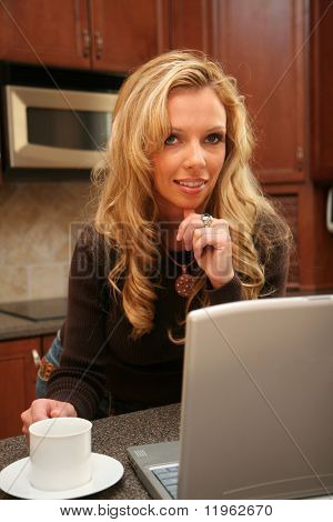 Woman drinking coffee standing in her luxury kitchen and working on her laptop