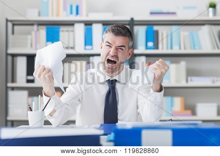 Angry Businessman Working At Office Desk