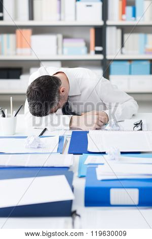Exhausted Businessman Sleeping On His Desk