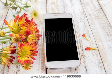 Smart Phone And Fresh Flowers On Wood Table