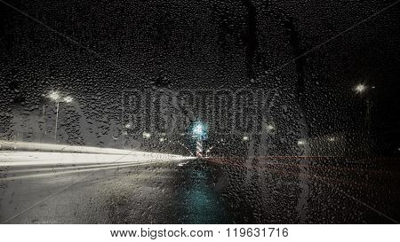 Night View Of The Road Through Glass With Raindrops