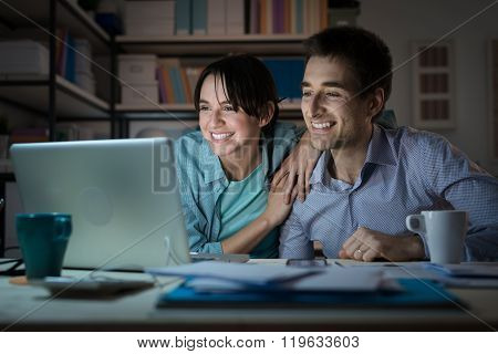 Happy Young Couple Surfing The Web At Home