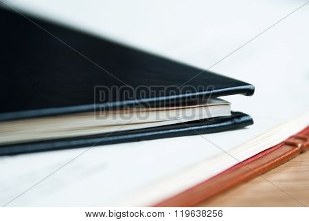 Black Leather Notebook Lies On An Open Notebook With White Sheets