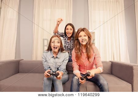 Three Happy Attractive Girls Playing Video Games At Home
