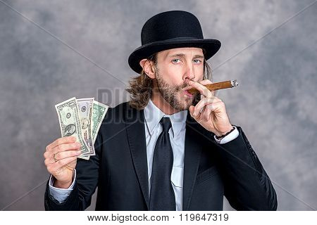 Businessman With Bowler Hat In Black Suit Showing Money And Smoking Big Cigar
