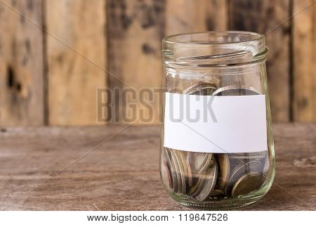 Coins In A Glass Jar On Wooden Table