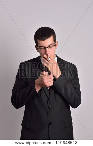 Young Man Dressed In Tuxedo Lighting Cigarette In Studio