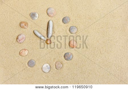Watch With Stones Laid On The Sand As A Background