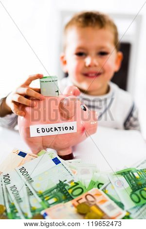 Saving concept. Child puts money in piggy bank. Selective focus. Saving for a education