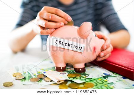 Saving concept. Women's hand puts money in piggy bank. Selective focus. Saving for a education