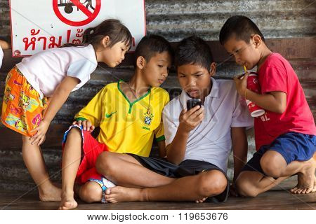 SANGKHLABURI, THAILAND, JANUARY 24, 2016 : A group of Thai kids is watching or playing on a smartphone under the hall of the Mon bridge in Sanghlaburi, Thailand