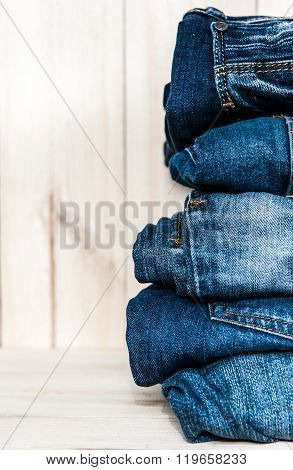 stack of various shades  blue jeans on wooden background
